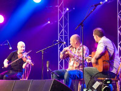 Michael McGoldrick, John McCusker and John Doyle performing at the Cambridge Folk Festival 2014. (Photo by Charles Sturman)