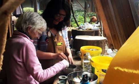 Two people do arts and crafts together in a shed surrounded by plants and wood