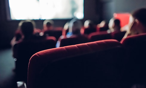 Photo of a small cinema with red chairs and a few people looking at a screen
