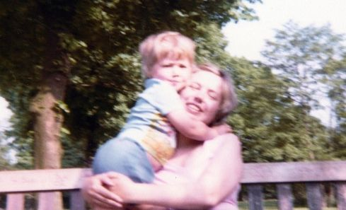 A mother hugs her young son on a park bench in the documentary, Irene's Ghost