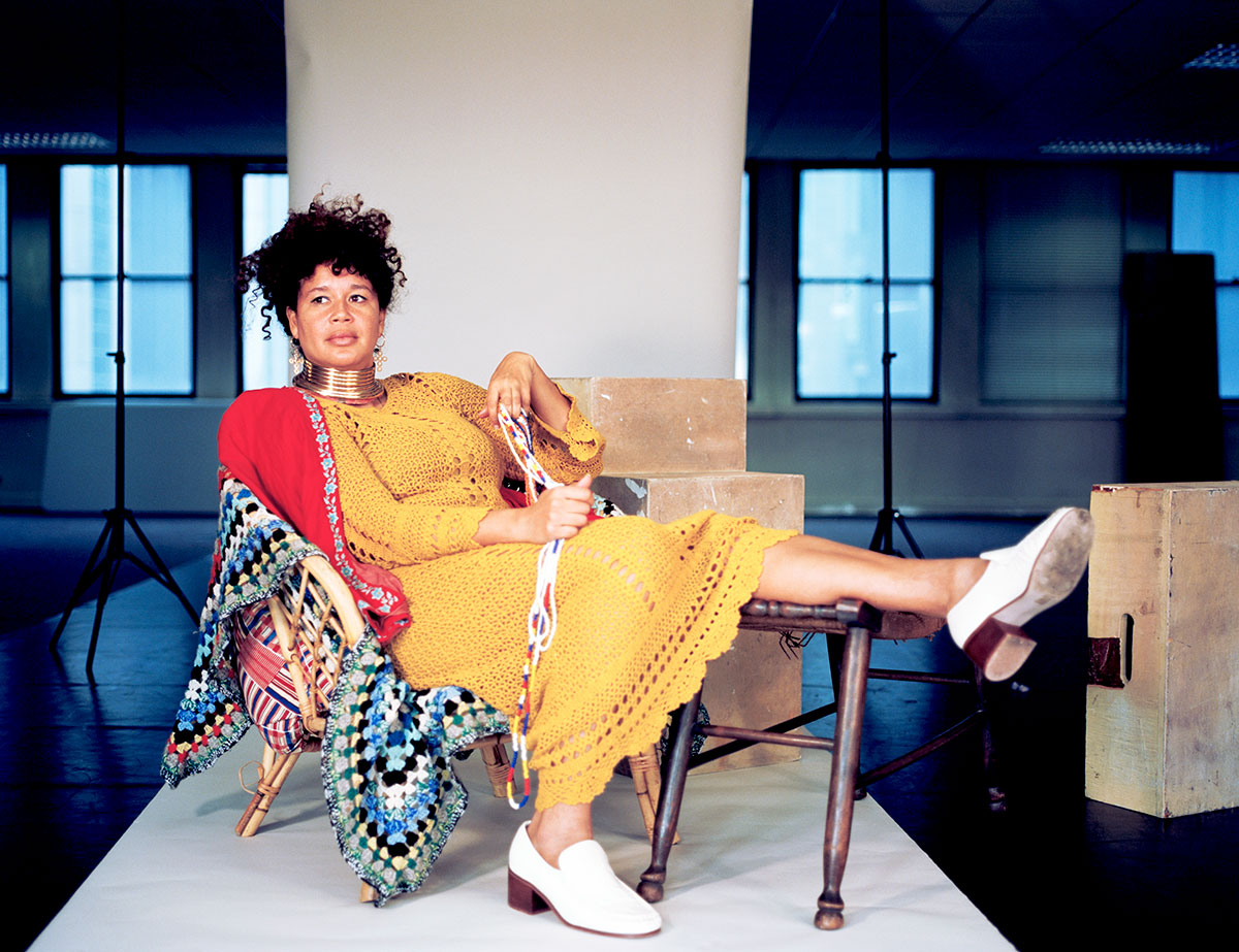Photo of Artist Alberta Whittle, sitting down with her leg up on a table