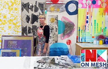 Lorna Brown stands in a studio surrounded by brightly coloured artwork