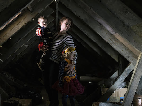 Grief: A Glimpse. Photo of a Woman and two young children in an attic