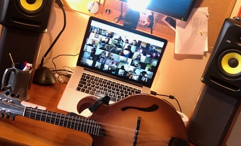 A guitar sits in front of a laptop which shows a series of faces participating in a Zoom call