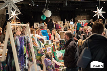 Photo from Flock event, showing lots of people and fabrics in a barn