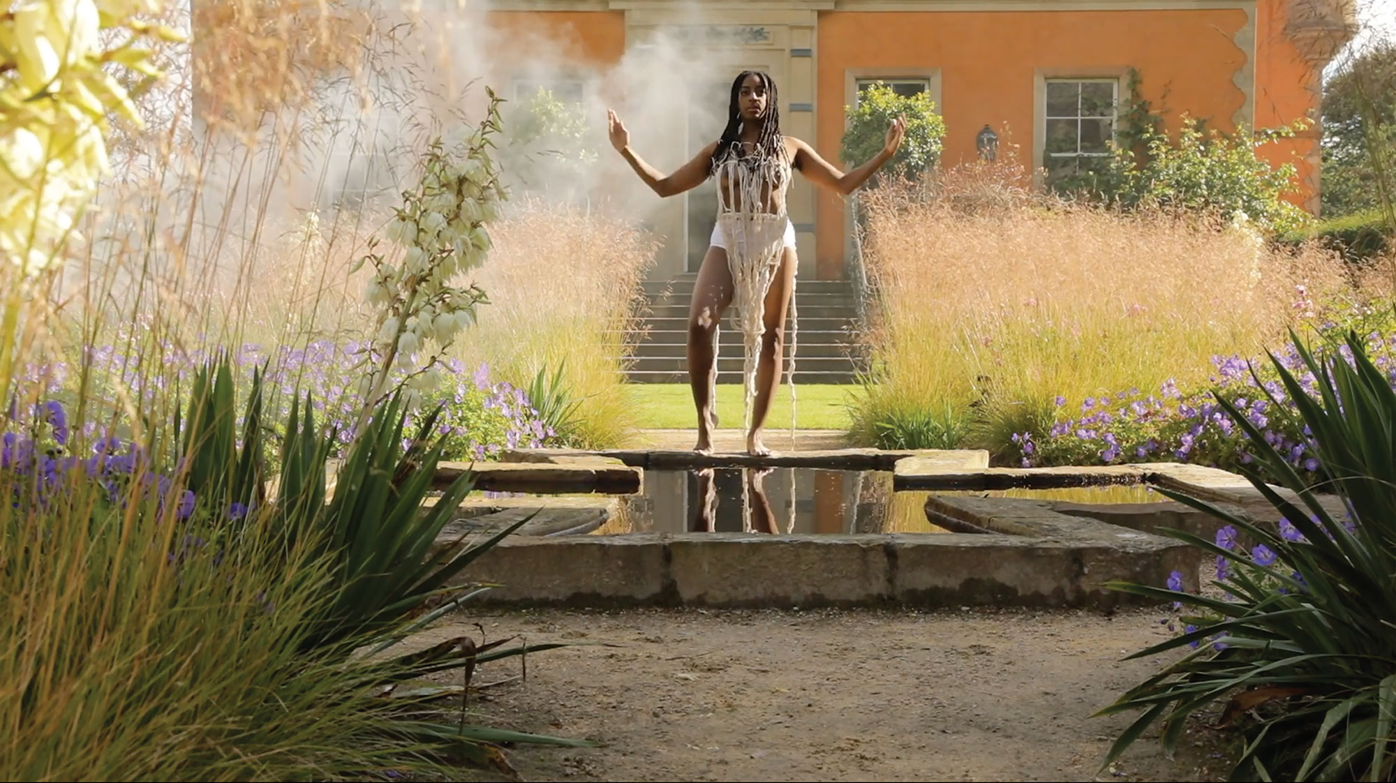 A still image from Alberta Whittle's 'RESET: 2020' showing a woman in a garden with her arms raised