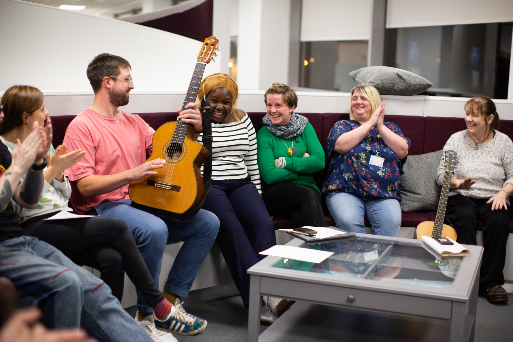 A group of people sit on a sofa clapping - one is holding a guitar - they look excited