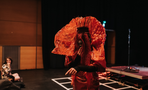 A person stands on stage holding a microphone with their face covered by orange material