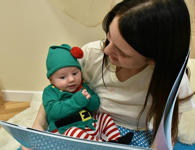 A mother reads to a baby who is dressed like a tiny elf