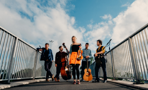 A band stands on an overpass in bright sunshine with their instruments