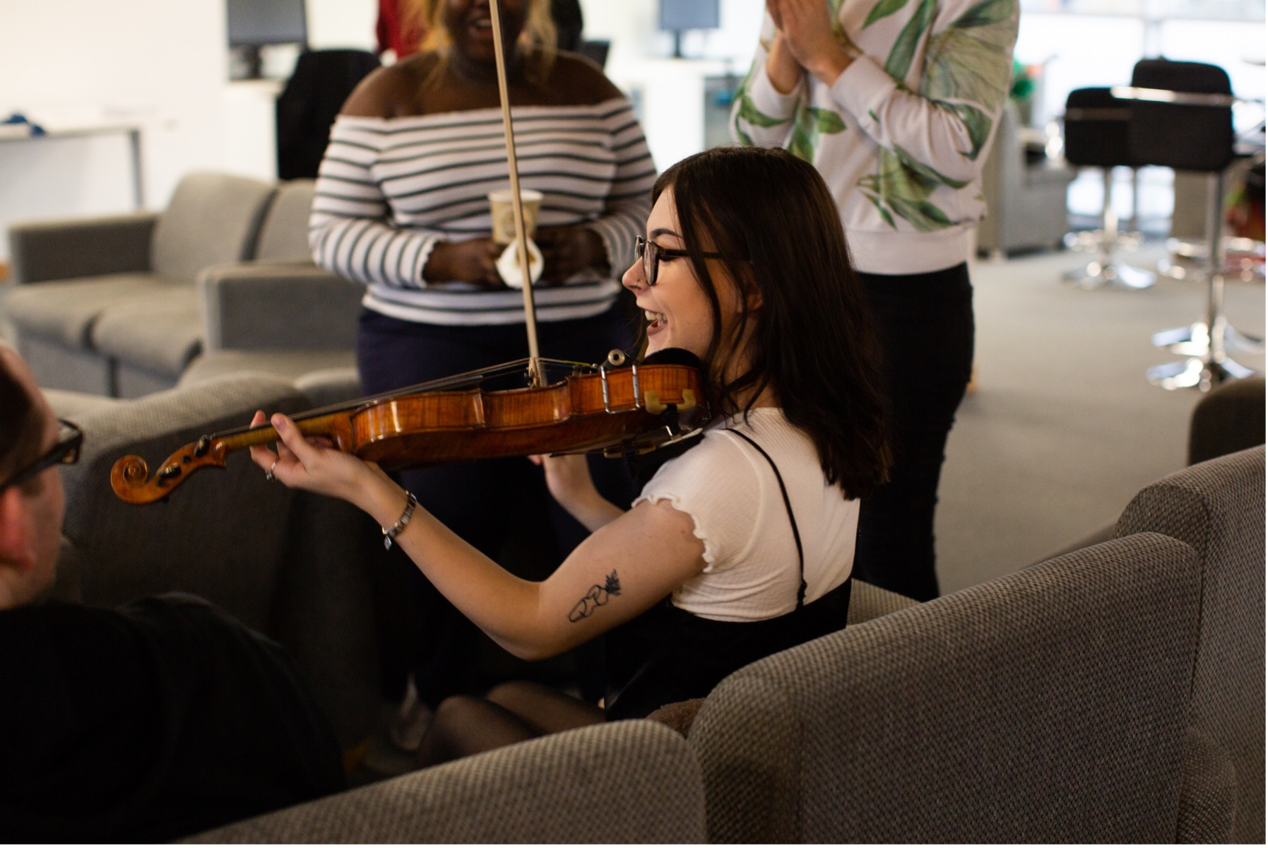 Steph sits on a sofa and plays violin - she is smiling
