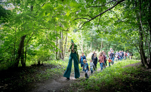 A performer on stilts leads a group through the forest