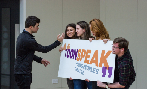 Four people holding up a Toonspeak banner as one person directs for a photo