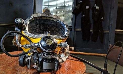 A diver's mask sits on a table in the interior of a ship