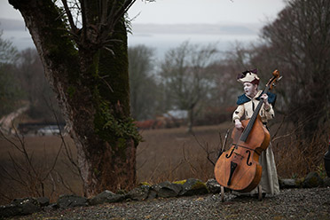 Photo of a person in costume playing a cello in the woods