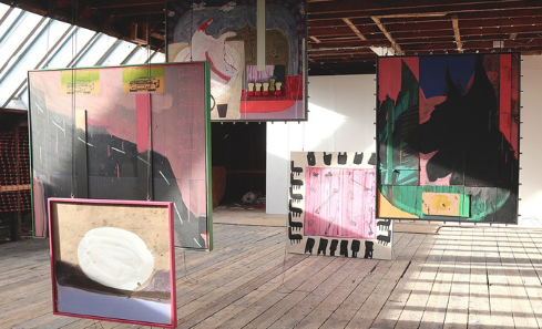 Various colourful artworks are displayed in a loft warehouse space