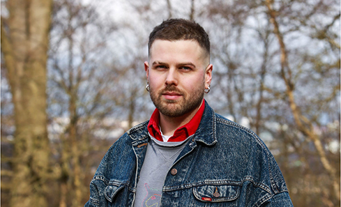 Photo of Andrew Black, standing outside smiling and wearing a denim jacket