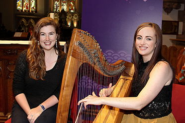 Photo of two young women smiling into the camera, the one on the right is playing a harp