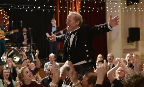 Peter Mullan stands up celebrating in a crowd in Sunshine on Leith