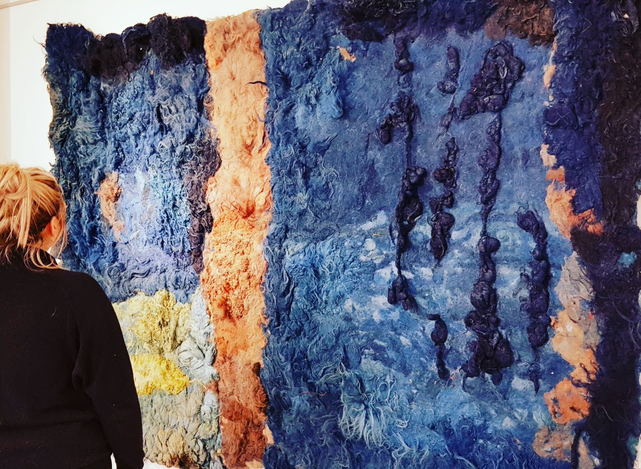 A woman stands in front of a large piece of orange and blue textured fabric