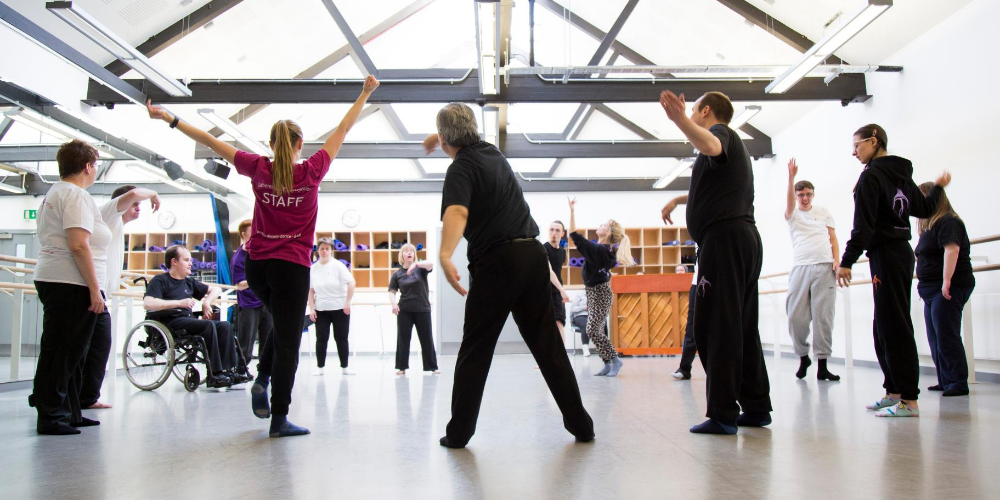 A group of dancers stand in a circle in a light and airy rehearsal room