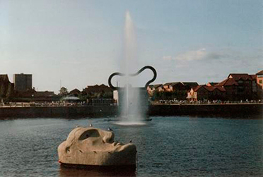 Floating Head: a large stone head is in the foreground, behind it a fountain shoots out water in the middle of a reservoir