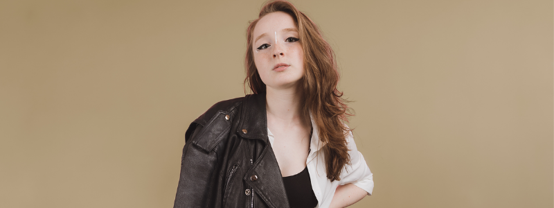 Zoe Graham stands in front of a light brown wall with a leather jacket thrown over one shoulder