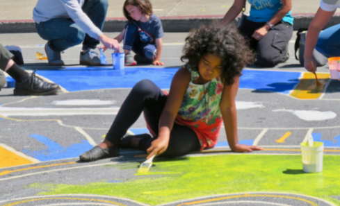 A young girl with curly black hair painting a picture on the ground.