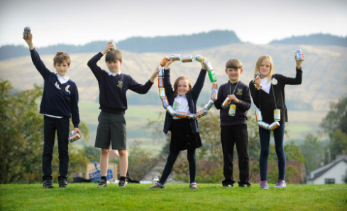 Five primary school children standing on a field creating letter with their body and a string of cans.