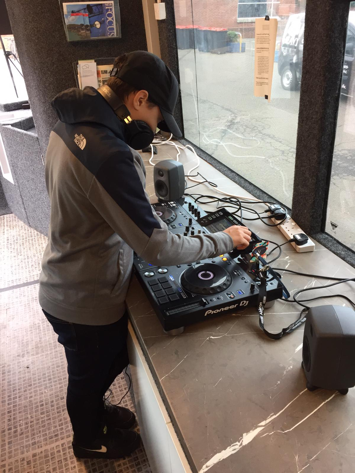 A young person uses mixing decks
