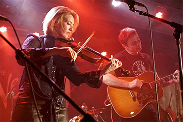 A woman plays the violin and a man plays a guitar on stage