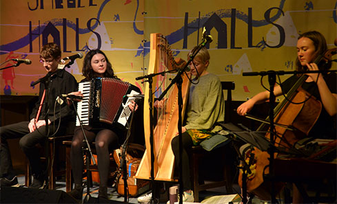 A group of musicians play on a stage