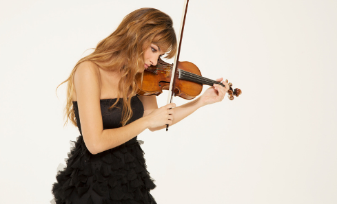 Nicola Benedetti stands in a black formal strapless dress holding her violin in playing position