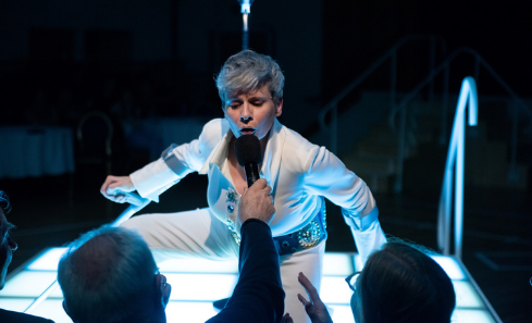 Artist Claire Cunningham in a white Elvis style suit on stage with a microphone being held up to her by one of the audience members