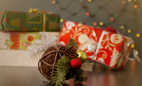 A brown christmas bauble in front of a Christmas present, with red and white wrapping paper
