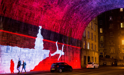 A white silhouette of a woman standing on a cliff illuminated with pink lights on the Cowgate walls
