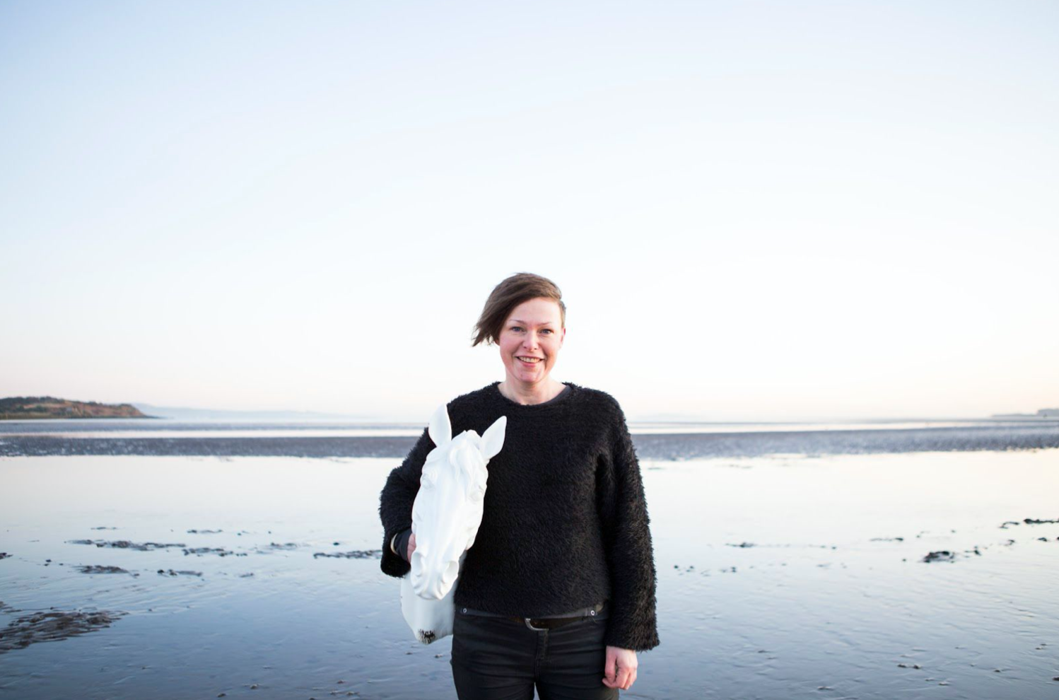 Amy Duncan stands on a beach, holding a fake white horse head