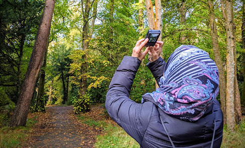 A woman takes a photo on her phone in the woods