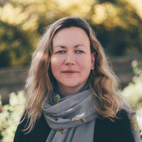Writer Helen Sedgwick stands wearing a grey scarf, her hair tumbling around her shoulders with light falling on her face and in the background in an outdoor space with trees and bushes