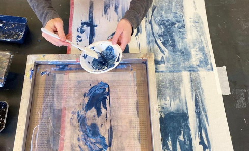 Someone stands holding a bowl of blue ink which they are about to brush onto a frame for screen printing