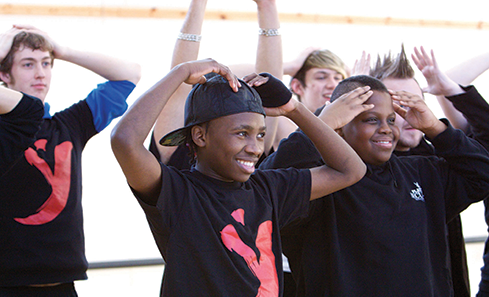 Photo of a group of children with their hands on their heads