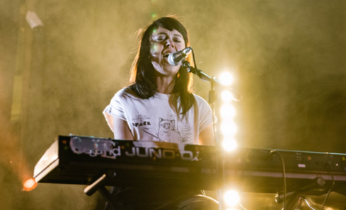A person stands in front of yellow lights on a stage singing into a microphone and playing a keyboard.