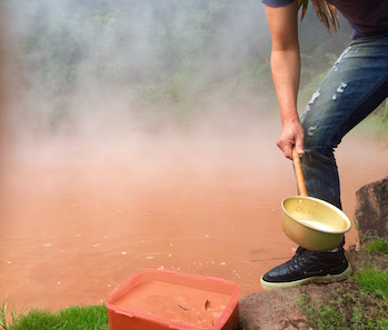 Collecting bloody-red mud at Bloody Pond Hell in Beppu.