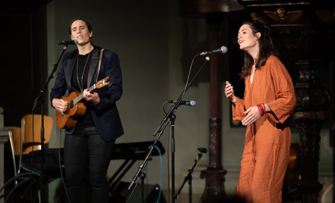 Rachel Sermanni and Rose Cousins stand on stage playing guitar and singing