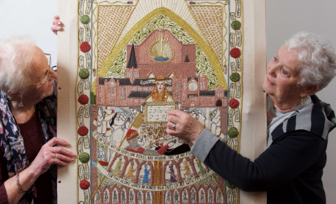 Two women stand in front of the tapestry they embroidered commemorating 700 years of the declaration of Arbroath