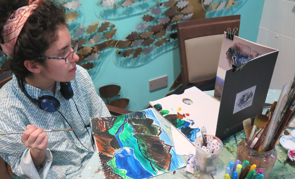 A person sits in front of a colourful painting of a seascape that they are working on
