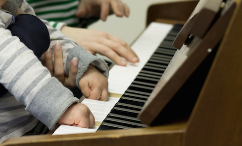 Young hands on piano. Credit: Nordoff Robbins Music Therapy
