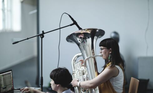 A woman playing a tuba during a recording session