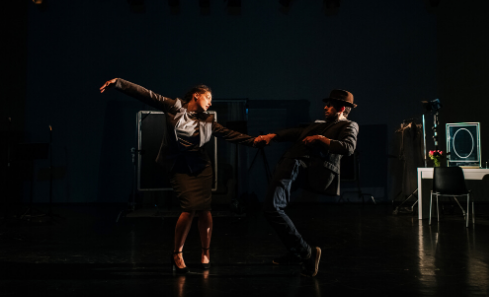 Two people in business wear dance on stage