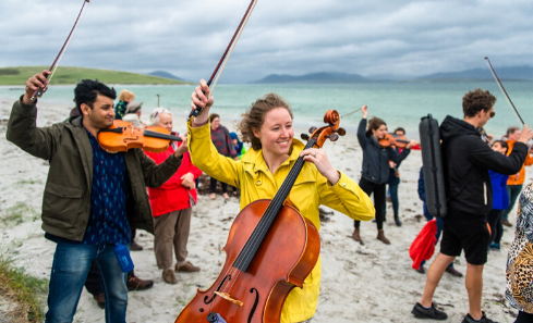 A group of musicians play their instruments on the beach